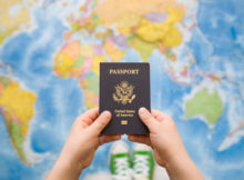child's hand holding us passport. map background. ready for traveling. open world.